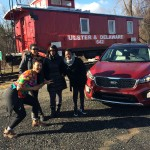 four black women laughing in front of a red kia sorento suv