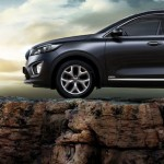 Kia Sorento SUV parked on a cliff overlooking a sunset