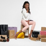 African-American stylist Stephanie Alexis sits atop a pile of luggage dreesed in heels and tight pink jeans.