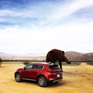 Red Kia Sportage for SimplyRides.com in the desert with metal elephant